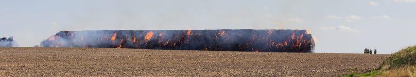 Stapelhooi in brand op gebied met firemans stock foto