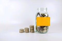 Stapeln der Münze und der Münze in der Flasche mit klebriger Anmerkung stockbild