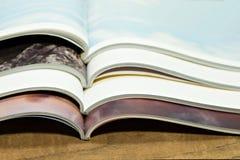Stapeln des Zeitschriftenplatzes auf Holztischhintergrund lizenzfreie stockfotos