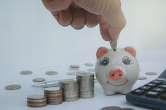 Stapeln Sie Münze mit Handtropfen die Münze in Sparschwein finanziell Lizenzfreie Stockfotos