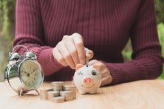 Stapeln Sie Münze mit Handtropfen die Münze in Sparschwein finanziell Lizenzfreies Stockfoto
