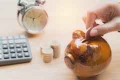 Stapeln Sie Münze mit Handtropfen die Münze in Sparschwein finanziell Stockfotografie