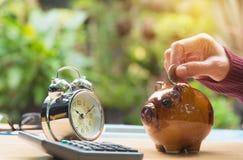 Stapeln Sie Münze mit Handtropfen die Münze in Sparschwein finanziell Lizenzfreie Stockfotografie