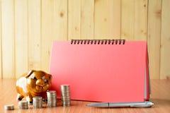 Stapeln Sie Münzen, Taschenrechner und Sparschwein auf hölzerner Tabelle und Kopien-SP Stockbild