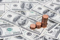 Stapeln Sie US-Pennys in einem steigenden Balkendiagramm auf Hintergrund mit Geldamerikaner hundert Dollarscheine Lizenzfreie Stockfotos