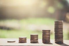 Stapeln von den Münzen und von Geld, die für die Rettung, Münze im Glas-bottl wachsen Lizenzfreies Stockfoto