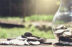 Stapeln von den Münzen und von Geld, die für die Rettung, Münze im Glas-bottl wachsen Lizenzfreie Stockfotos