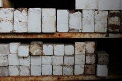 Stapels ceramische ovenbakstenen op geroeste metaalplanken Royalty-vrije Stock Foto's