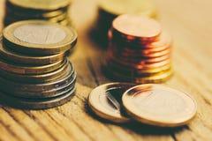 Stapels Glanzende Witte en Gele Euro Muntstukken van Verschillende Waarde op Houten Achtergrond De Begroting van de Voorradenbesp stock foto