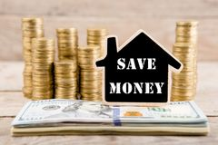 Stapels muntstukken en dollarrekeningen, bord in de vorm van een huis met tekst & x22; SAVE MONEY& x22; Royalty-vrije Stock Afbeeldingen