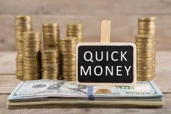 Stapels muntstukken en dollarrekeningen, bord met tekst SNEL GELD stock fotografie