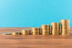 Stapels muntstukken op een houten lijst Bedrijfsconcept en de groei van kapitaal stock afbeeldingen