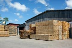 Stapels van gestapeld ruw besnoeiingstimmerhout bij een zaagmolen stock afbeeldingen