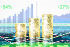 Stapels van gouden muntstukken op het scherm met bedrijfsgrafiek bij zaken Stock Afbeelding