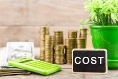 Stapels van muntstukken en dollarrekeningen, calculator, bord met tekst & x22; COST& x22; stock foto