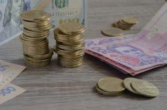 Stapels van muntstukken Oekraïense hryvnia en Amerikaanse dollars royalty-vrije stock foto's