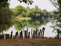 Stapels van omheining op bank van het meer Stock Afbeelding