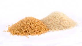 Stapels van Ongepelde rijst en Witte Rijst Stock Foto
