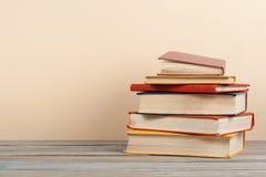 Stapla för bok Den öppna inbundna boken bokar på trätabell- och beigabakgrund tillbaka skola till Kopieringsutrymme för annonstex Arkivbild