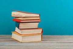 Stapla för bok Den öppna inbundna boken bokar på trätabell- och blåttbakgrund tillbaka skola till Kopieringsutrymme för annonstex Royaltyfri Bild