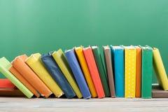 Stapla för bok Den öppna inbundna boken bokar på trätabell- och gräsplanbakgrund tillbaka skola till Kopieringsutrymme för annons royaltyfri foto