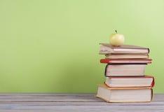 Stapla för bok Den öppna inbundna boken bokar på trätabell- och gräsplanbakgrund tillbaka skola till Kopieringsutrymme för annons Arkivbilder