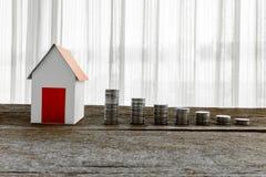 Stapla mynt och hemmet modellera för sparande med växande pengar royaltyfri fotografi