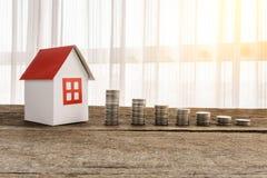 Stapla mynt och hemmet modellera för sparande med växande pengar arkivfoton