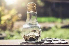 Stapla mynt och pengar som växer för sparande, mynt i glass bottlle royaltyfri fotografi