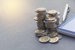 Stapla myntet med penn- och anmärkningsboken på tabellen Finansiellt accountin royaltyfri bild