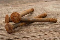 Stapla rostiga metallskruvar på lantligt trä arkivbild