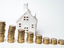 Stapla tornet och hus för guld- mynt, sparande pengar och lån för konstruktionsfastighet och hem- begrepp arkivfoton