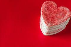 Staplad hjärta formade valentinkakor på röd bakgrund royaltyfri fotografi