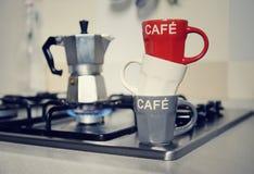 Staplad kaffekopp och tappningkaffekanna på kökugnen Arkivbilder