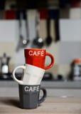 Staplad kaffekopp och tappningkaffekanna på kökugnen Arkivbild