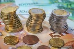 Staplade en och två euromynt med pappers- sedlar Royaltyfria Bilder