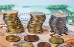 Staplade en och två euromynt med pappers- sedlar Arkivfoton