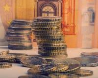 Staplade euromynt mot ett pappers- euro för valörvärde femtio Royaltyfri Bild