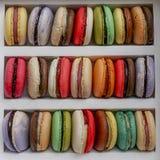 Staplade flerfärgade kakor för macarons i ask arkivfoto