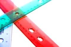 Staplade genomskinliga gröna och röda plast- linjaler för rosa färger som, isoleras på en vit bakgrund med rum för text Fotografering för Bildbyråer