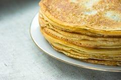 Staplade guld- kräppar på den vita plattan på bakgrund för linnetorkduk, closeup, frukost Royaltyfri Bild
