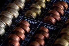 Staplade mynt i en metallisk kassaskrin med ett lås arkivfoton