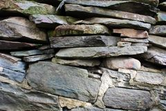 Staplade och mortared grå färger stenar, och plant vagga väggen Royaltyfria Bilder