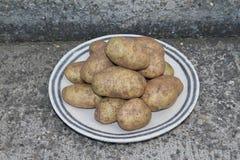 Staplade potatisar på a på en platta på konkreta moment Arkivfoto