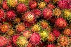 Staplade röd frukt för rambutanen ont-överkanten av de royaltyfri foto