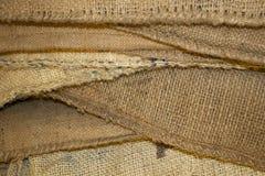 Staplade säckvävkaffepåsar av olika texturer och färger av brunt - bakgrund royaltyfria foton