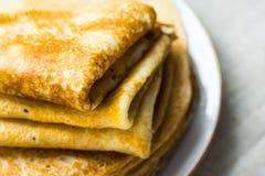 Staplade vikta kräppar på den vita plattan på bakgrund för linnetorkduk, closeup, frukost Fotografering för Bildbyråer