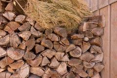Staplade wood journaler med torrt sörjer trädfilialen mot träpaneler Huggit av vedträ Vedtravebegrepp arkivbild