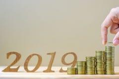 """Staplar sättande och redovisande pengar för affärsmannen med bakgrund för """"2019â€-numret, guld- mynt på trätabellen affär inve arkivfoto"""