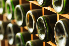 Staplat av gamla vinflaskor i källaren arkivbild